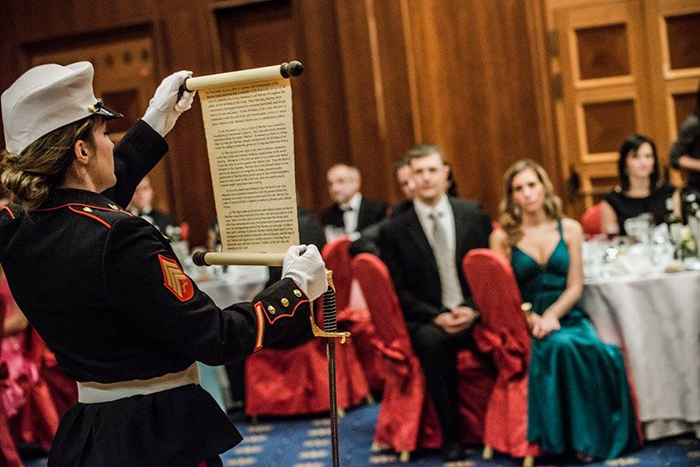 Sgt. Lyday stands with an open scroll to read a message for the 240th U.S. Marine Corps Ball in Prague.