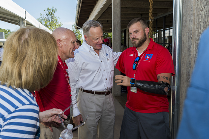 Ross Perot Jr. and other Memorial Day picnic attendees chat with retired Army Staff Sgt. Travis Mills.